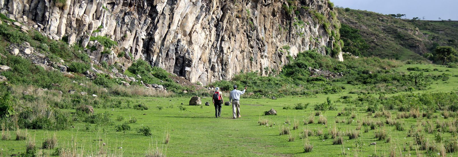 Two people walking outside in grassland with a cliff to the left