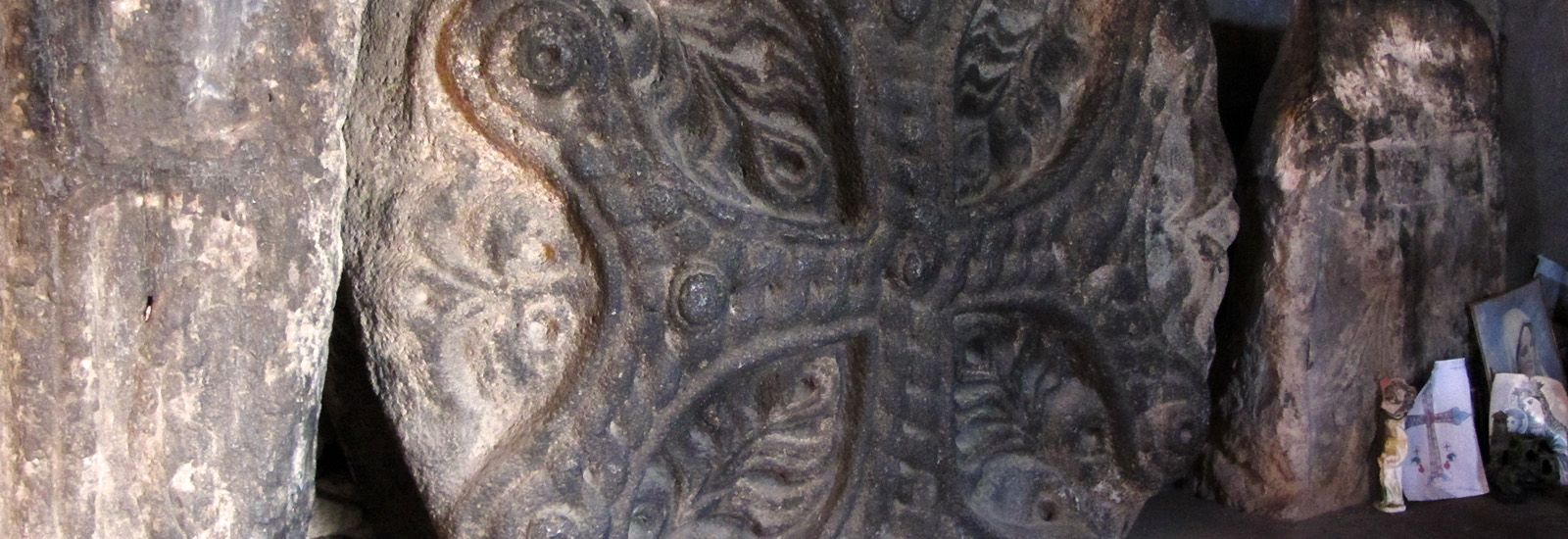 A close up of an old Cross stone
