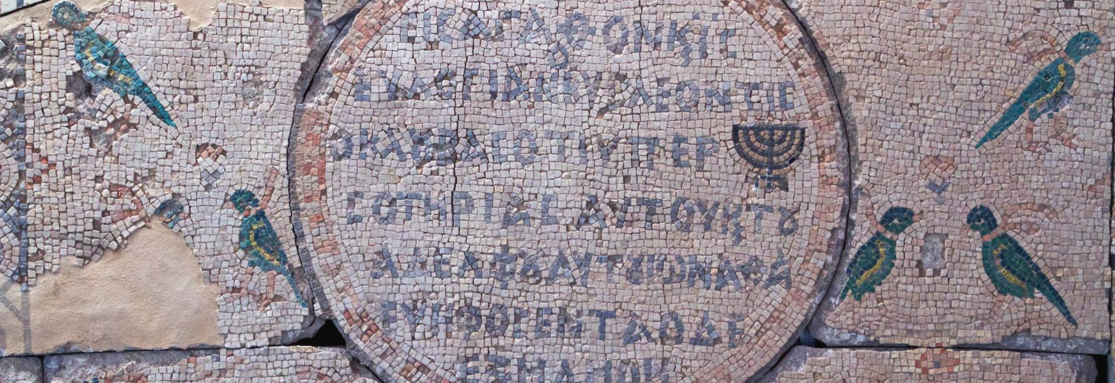 An old mosaic with birds and text