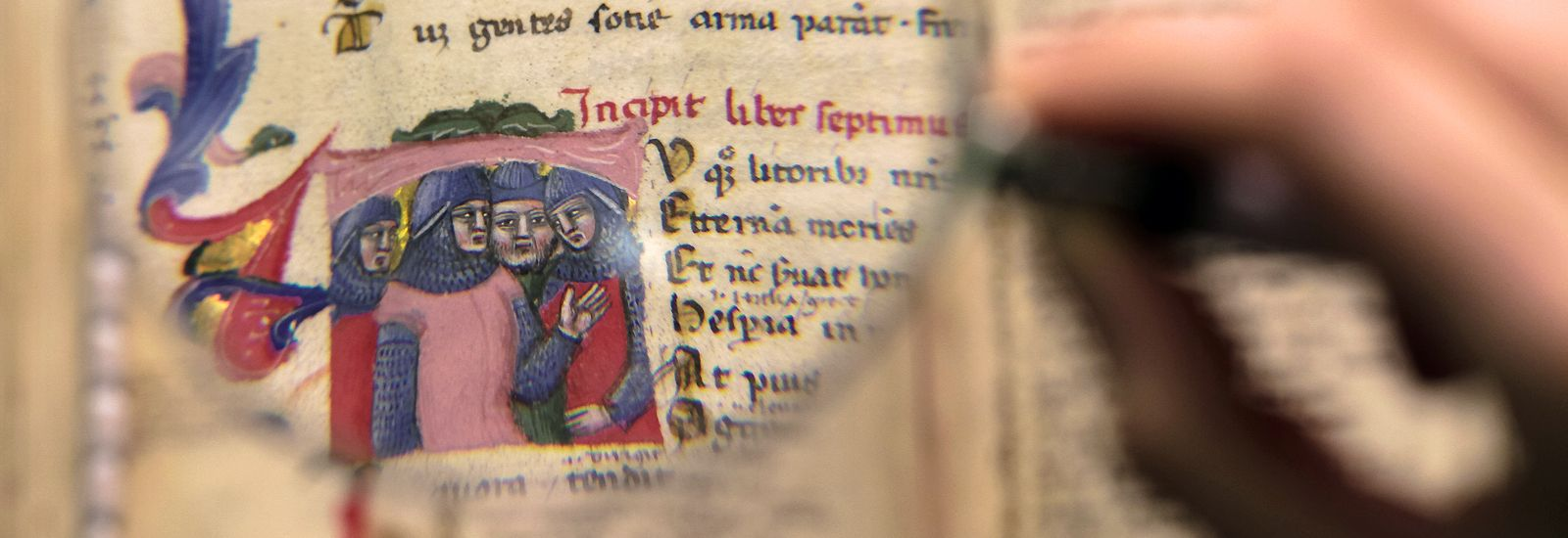 Magnifying glass showing a close up of text and figures on a manuscript