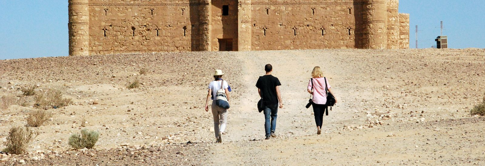 Three people talking toward a building in the desert