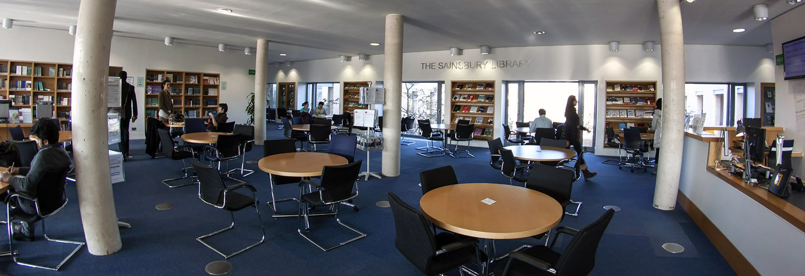 A wide shot of students and tables inside the Sainsbury Library
