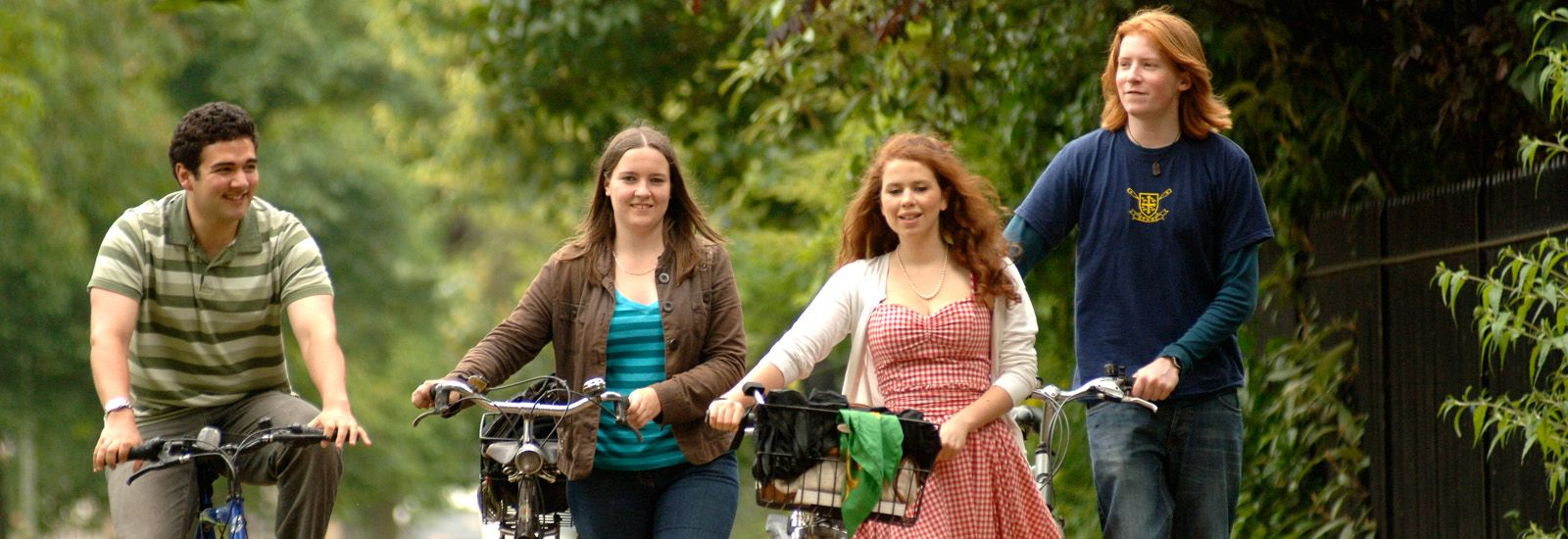 Four students walking with their bikes