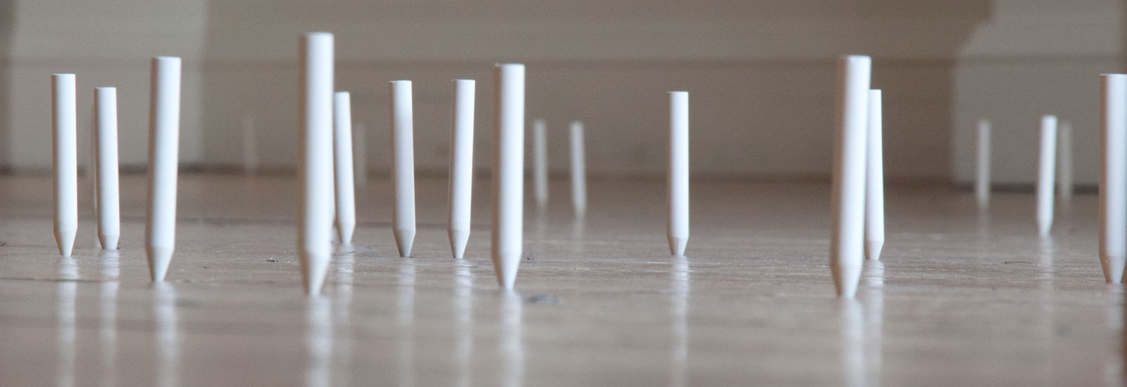 White cylinders on the floor as part of an artwork