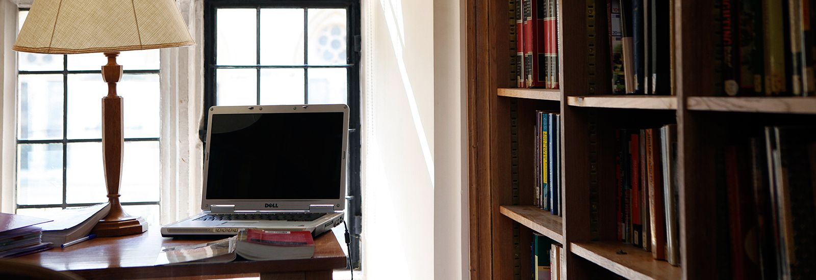 Lamp and laptop on a desk next to a bookcase
