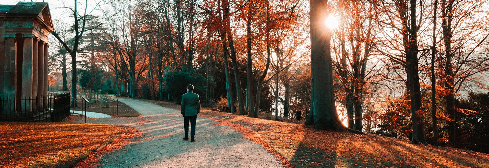 A person walking at sunset along a path in autumn