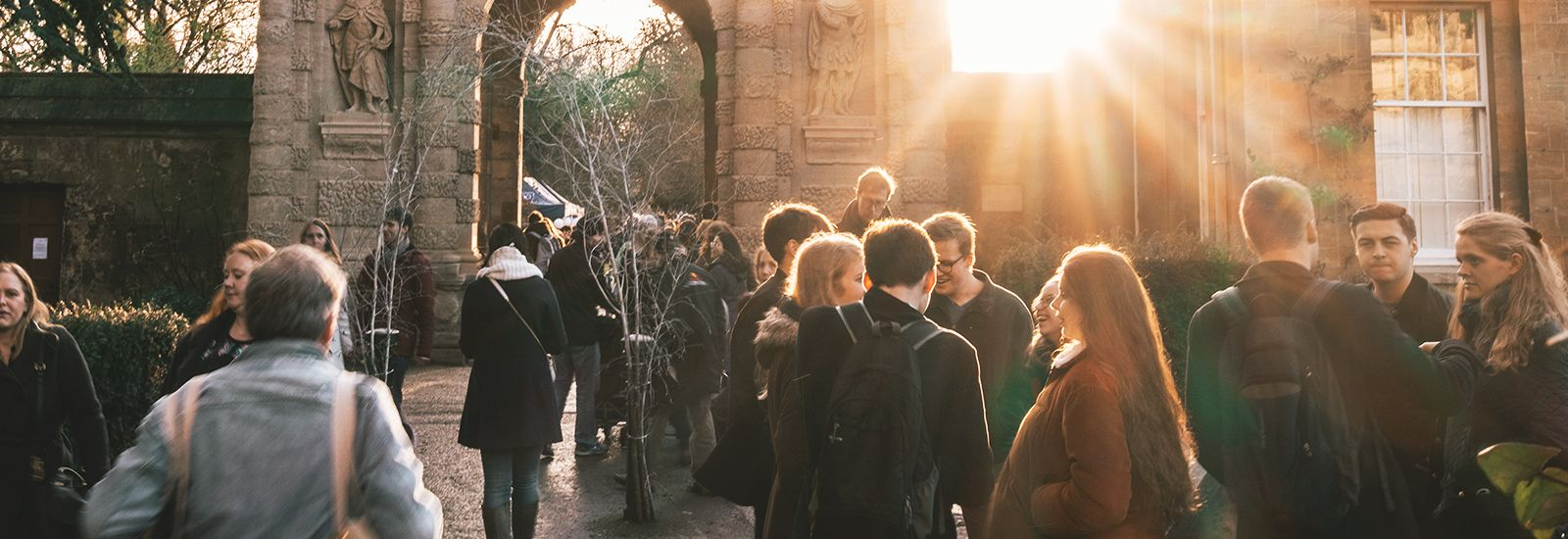 A photo of students standing near the archway entrance to the Botanic Gardens