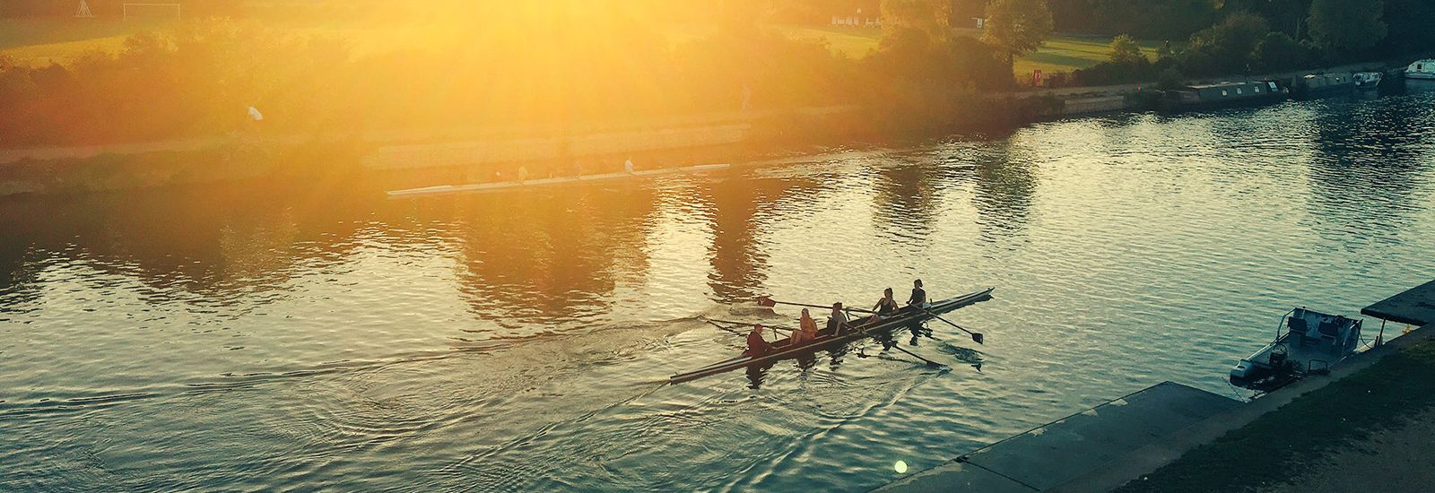 Students rowing up the river at sunset