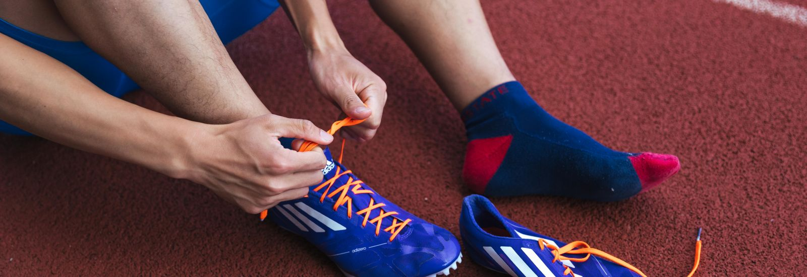 Student tying laces of running spiked on running track