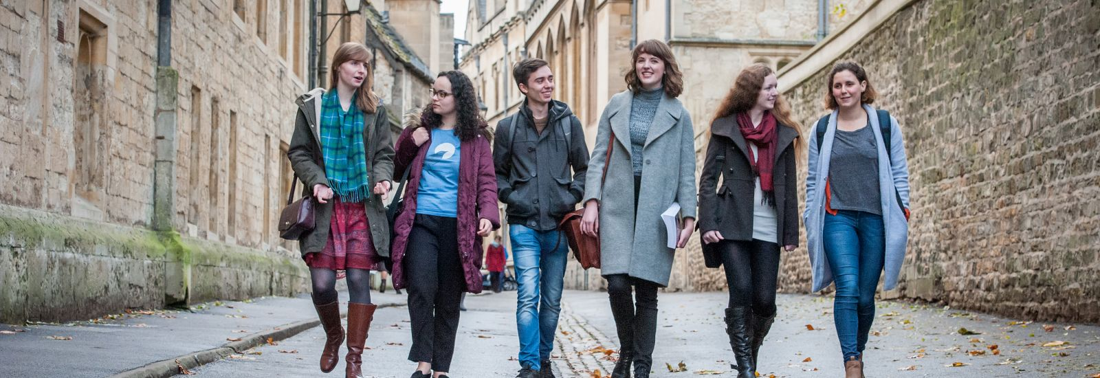 Six students walking to lecture along Brasenose Lane
