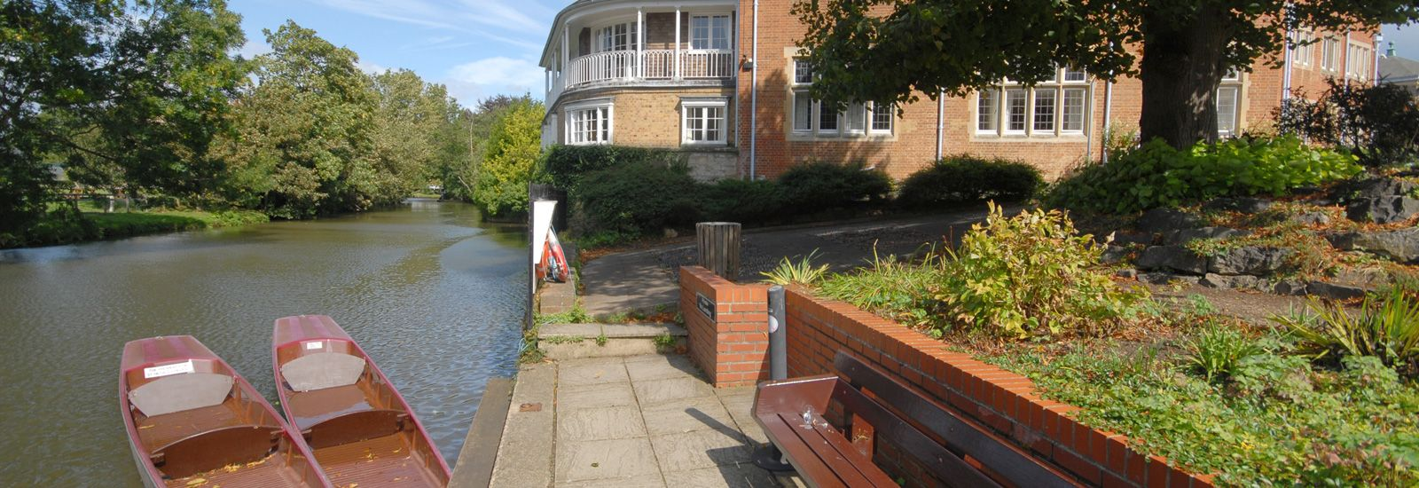 The riverside with two boats at St Hilda's College