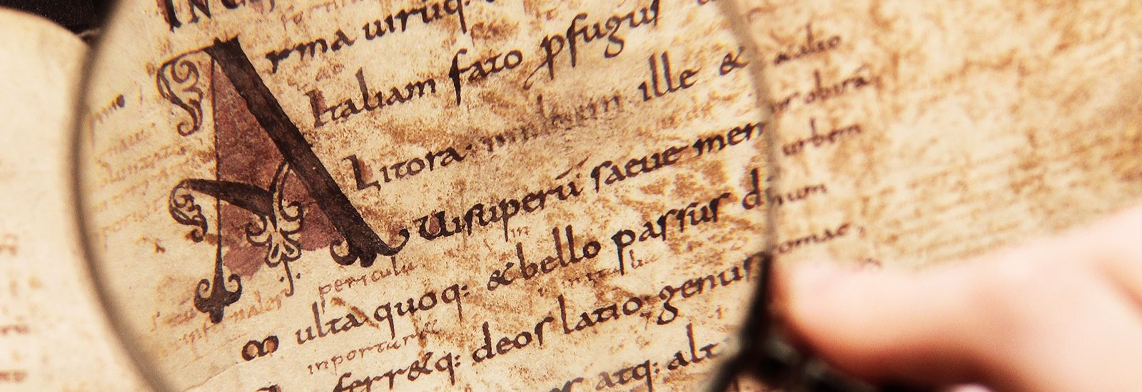 A close up of a magnifying glass over a latin manuscript