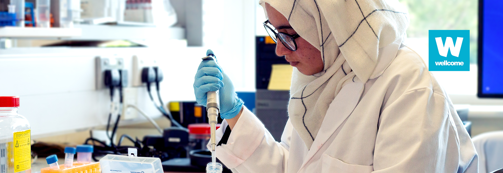 Student in a laboratory with the Wellcome logo