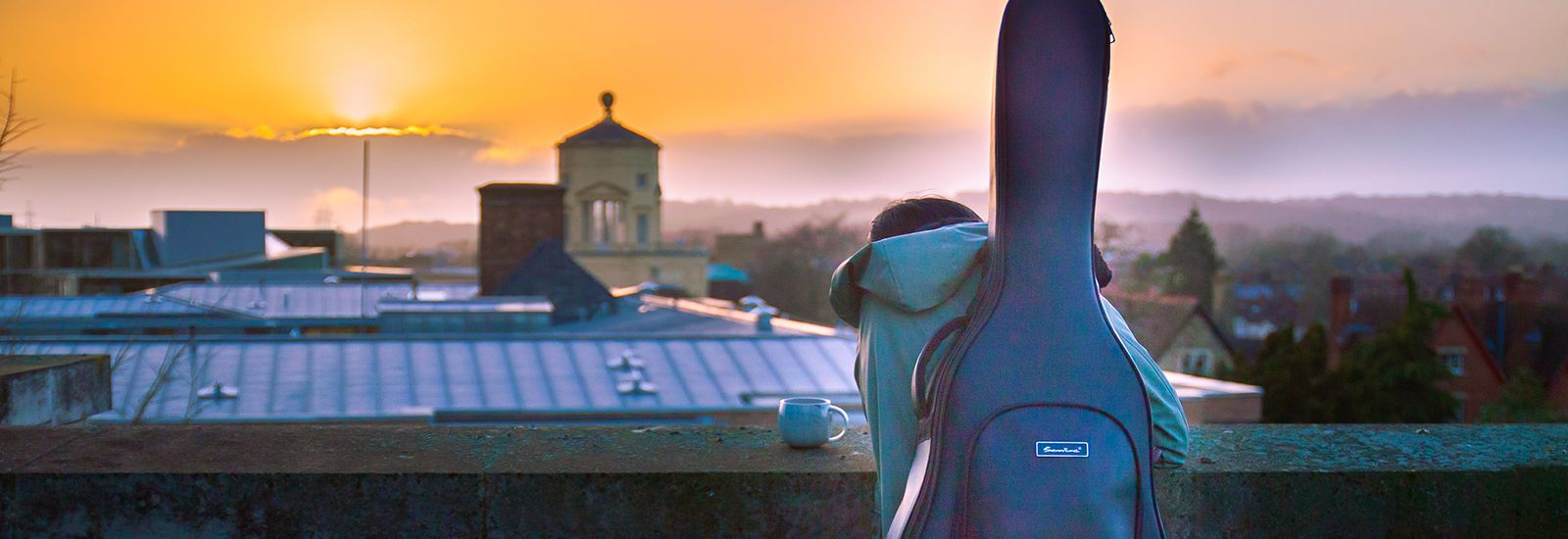 Student with a guitar case looking at rooftops at sunset