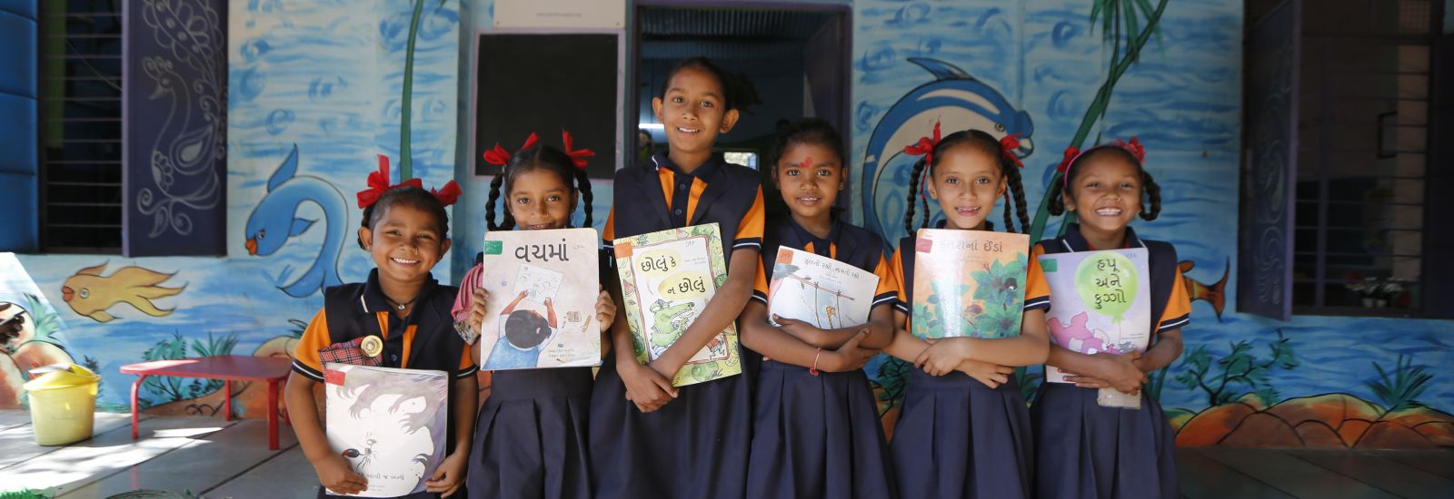 A group of schoolgirls clutching their books and smiling