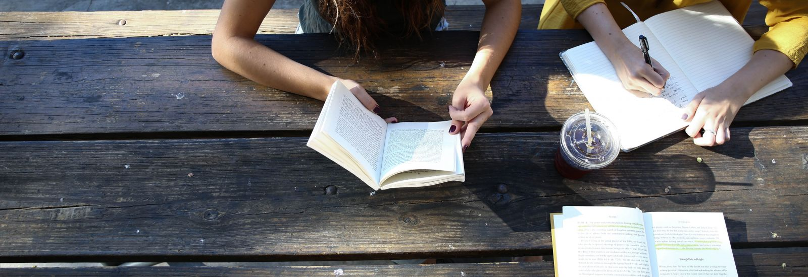 Three girls sitting around wooden table with open books
