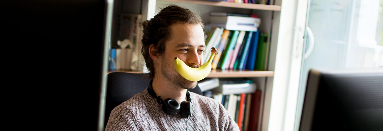 Student with banana on their face working on a computer