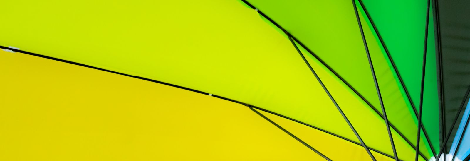 umbrella seen from below showing spokes and panels ranging from an orange through the spectrum to green