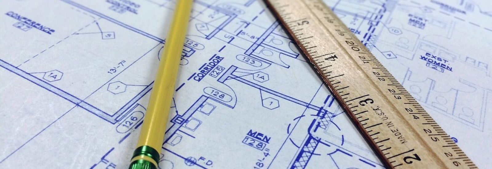 Image of a pencil and ruler on a 'blueprint' technical drawing