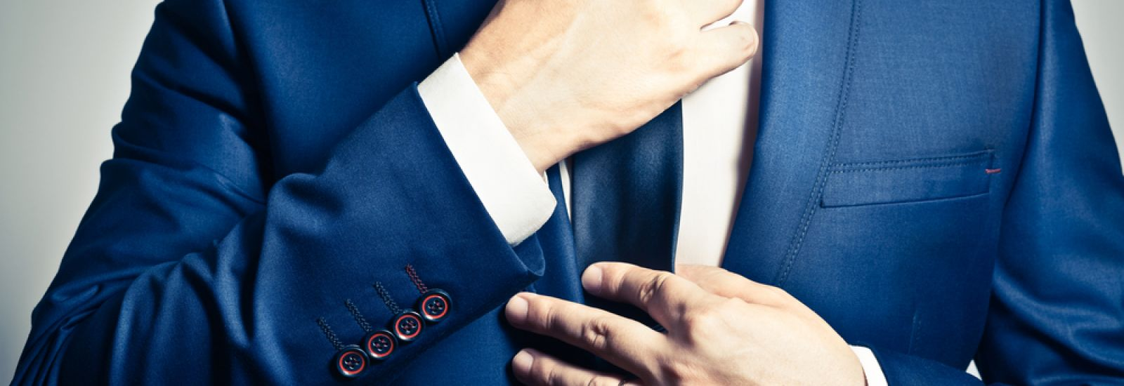 Businessman in blue suit tying the necktie: a ritual of sorts