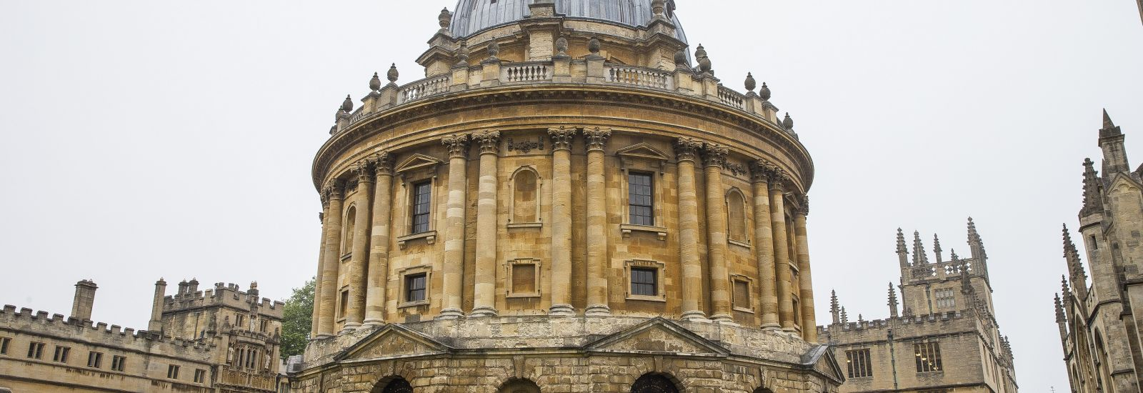 Landscape photo of the Radcliffe Camera and surrounding buildings with a cyclist in the foreground