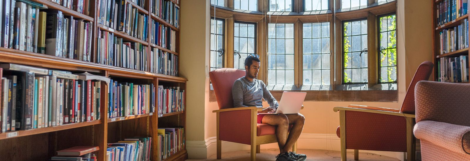 Student sitting with a laptop in the bay window of a library