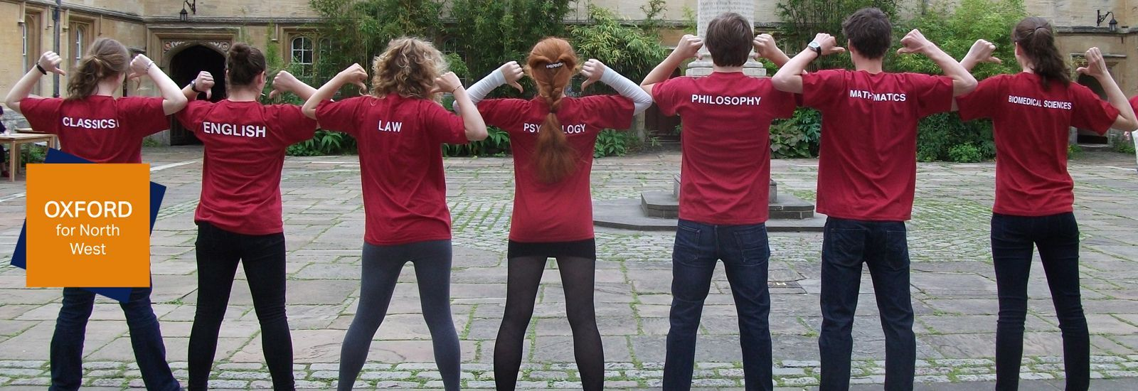 Seven students standing in a quad and pointing to the subjects written on the backs of their t-shirts.