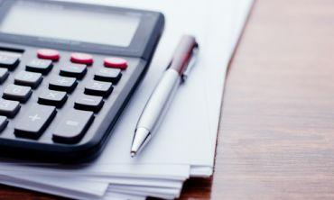 Calculator, pen and paper on desk