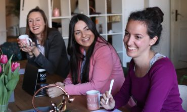 A group of three women sit at a table, smiling during an informal meeting. One is holding a cup of coffee, another is holding a pen. There are flowers on the table.