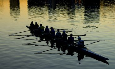 The silhouette of a team of rowers on the water
