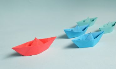 A red origami boat leads a group of four smaller blue origami boats