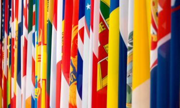 A close-up, colourful photograph of multiple international flags hanging side by side