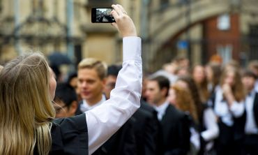 Student in academic dress takes a picture of Hertford Bridge