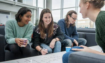 Group of friends sitting on sofas around a coffee table. Credits: University of Oxford