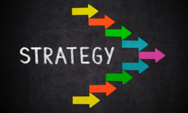 The word strategy is written in white chalk on a blackboard, surrounded by an arrow pointing to the right, which is made up of several smaller, multicoloured arrows