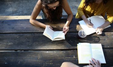 Three girls sitting around wooden table with open book