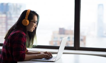 A person on their laptop, wearing headphones. Credits: Christina Morillo via Pexels