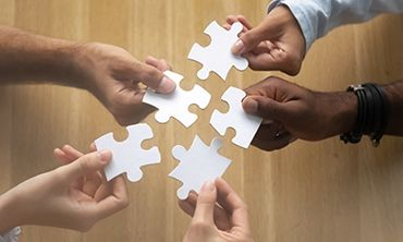 hands with a jigsaw puzzle