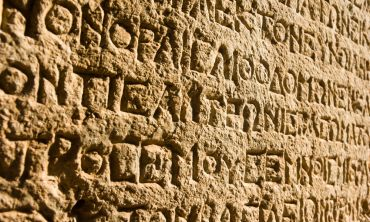 ancient Greek writing chiseled on stone