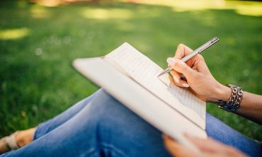 Image of someone writing in a notepad sat on the grass outdoors