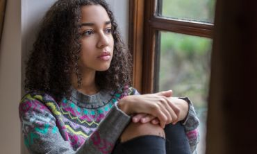 Adolescent girl looking thoughtful by window