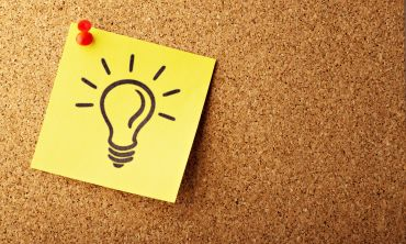 A light-bulb is illustrated on a bright yellow post-it note and pinned to a pinboard