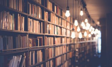 A long wall of bookshelves is lit softly by lots of hanging lightbulbs. The bookshelves are so long that they disappear into the distance.