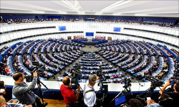 A panoramic view of the interior of the European Parliament, full of parliamentarians ahead of a vote. In the foreground a group of cameramen and photographers position their cameras onto the room.