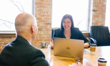 A formally-dressed man and woman smile and exchange conversation. The woman is using a laptop.