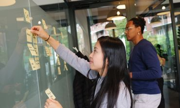 Two young researchers, representing different genders and ethnicities, map out a plan using post-it notes on a whiteboard