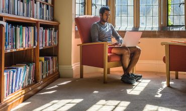 Student sitting in light by a library window