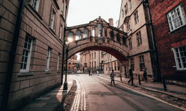 People walking under the Bridge of Sighs at sunset