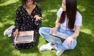 Two people sat on grass with their laptops.