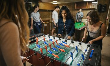 Female students playing table football in Jesus college JCR